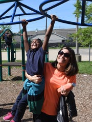 Volunteer Cathy Ross lifts up program participant Savanna