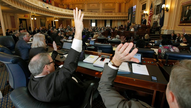 Members raise their hands to vote on a measure during the floor session of the Virginia House of Delegates inside the State Capitol in Richmond, Va. Feb. 11,.
