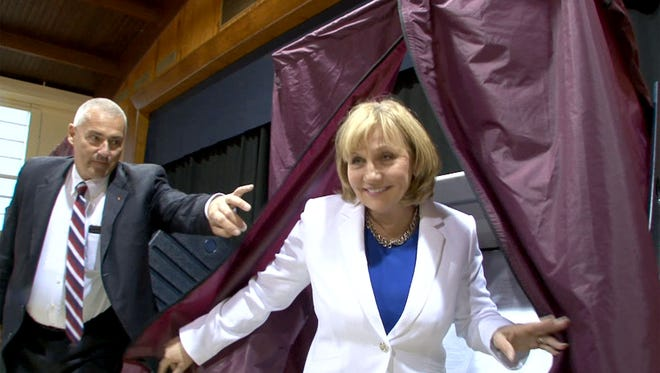 A State Trooper holds the curtain open for Republican Gubernatorial candidate and New Jersey Lt Governor Kim Guadagno after she cast her vote in the primary at the Church of the Precious Blood Parish Center in Monmouth Beach Tuesday, June 6, 2017.
