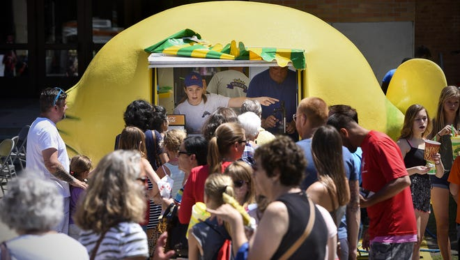 Kaitlin Hudalla helps customers at a lemonade stand in front of Stewart Hall during the 2016 Lemonade Concert and Art Fair at St. Cloud State University. A smartphone app will help visitors find vendors at this year's event, on Thursday.