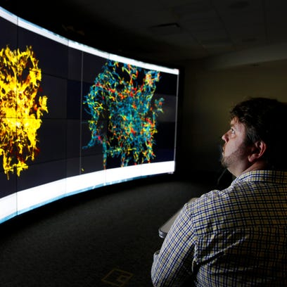 University of Rochester Astrophysics professor Adam Frank is silhouetted in front of the large computer screen displaying simulations showing massive star formation as he meets with his research group at the VISTA Collaboratory.