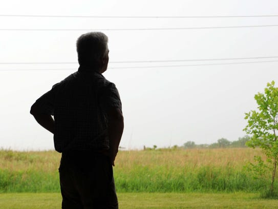 David Hague looks out on the prairie and wetlands that