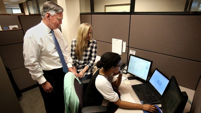 RBG managing partner John Griesbeck stops by to discuss a tax issue with staff accountantsTori Braswell (center) and Ambria Arnold on Oct. 19. Reynolds, Bone and Griesbeck stands out as smallest 2016 Top Workplace