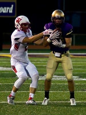 Albion College defensive back Josh Padelt makes an interception against Wabash College on Sept. 3.