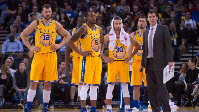 Golden State Warriors interim head coach Luke Walton (far right) stands with his team during a recent game.