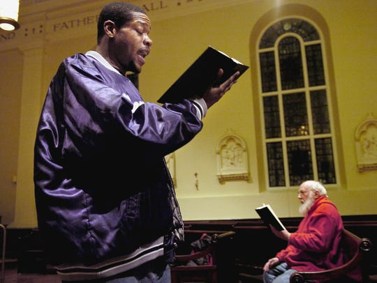 "Alphonso Miller sang ""Amazing Grace"" in honor of Thomasine Evans and Michael Wright during a memorial service in 2005 for the two at St. Vincent de Paul church. Deacon Edward Stoops (right) led the service by sharing his family's personal memeories of both Evans and Wright."