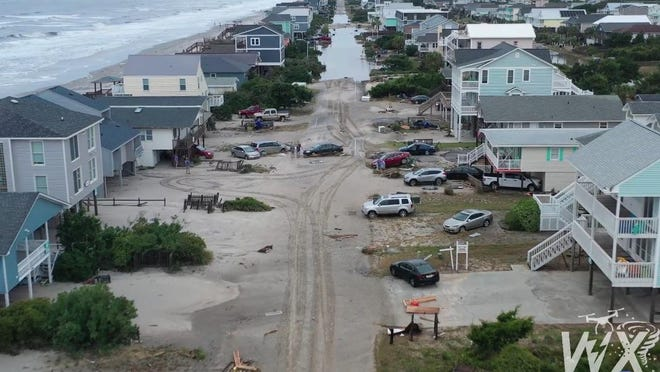 A drone video posted on the WXChasing Facebook page showed extensive storm surge on Oak Island, leaving the town covered in sand as far as the eye can see.