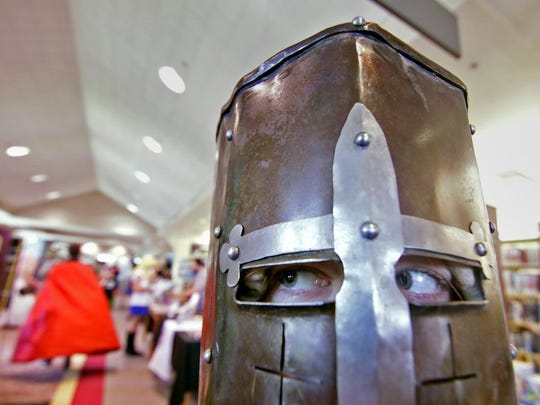 Alisa Petronis of Easley, dressed as the black knight from the movie 'Monty Python and the Holy Grail,' looks around booths of artists at Electric City ComiCon at the Anderson County Library in Anderson.
