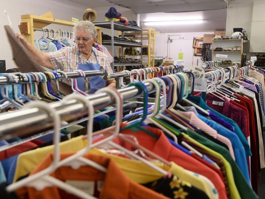 Francis Theony, a volunteer at the Emilie Center, sorts clothes Tuesday morning. The center is planning an Indian taco sale fundraiser April 22 for the St. Martin de Porres Mission.