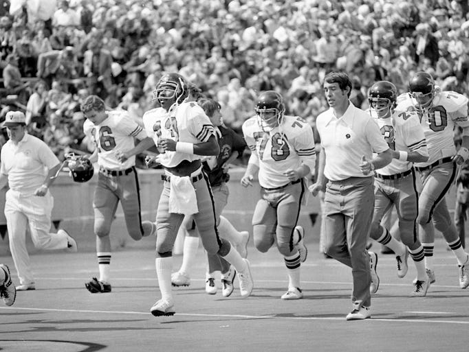 Steve Sloan's second season at the helm of the Vanderbilt program starts as the young Commodores head man, third from right, sprints onto the field for the UT-Chattanooga game on Sept. 14, 1974.