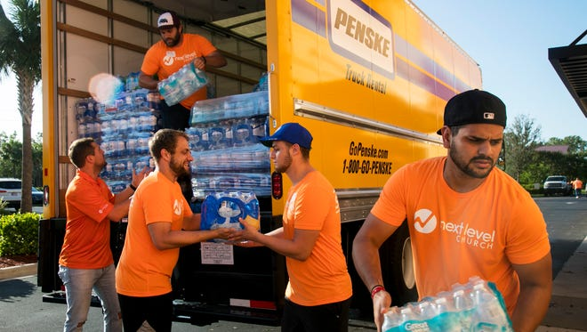 The Next Level Church Serve Team unloads a truckload of water on Tuesday to give to families in need following Hurricane Irma.