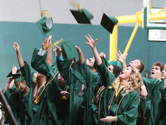 Graduates throw up their caps during the Regis High School commencement on Sunday, June 5, 2016, in Stayton.
