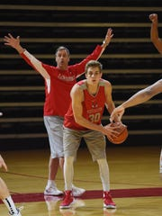 Marist's Ryan Funk looks to pass the ball as he is covered by assistant coach Andy Johnston during Tuesday's practice at Marist College.
