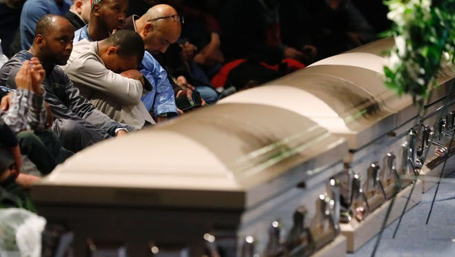 Mourners bow their heads during funeral services for three of the victims of the deadly shooting at the Quebec Islamic Cultural Centre, at the Congress Centre in Quebec City, Quebec, February 3, 2017.