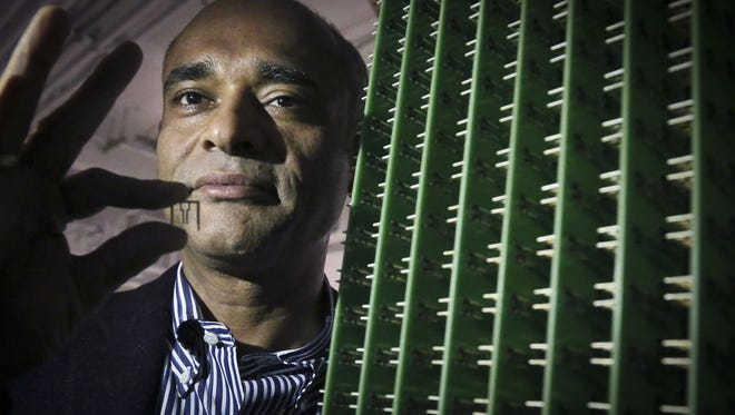 In this Dec.2012, photo, Chet Kanojia, founder and CEO of Aereo, Inc., stands next to a server array of antennas as he holds an antenna between his fingers, in New York.  Aereo is one of several startups created to deliver traditional media over the Internet without licensing agreements. Past efforts have typically been rejected by courts as copyright violations. In Aereo's case, the judge accepted the company's legal reasoning, but with reluctance.