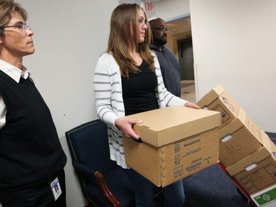 Carrying motions about drug convictions to the Attorney General's Office in Wilmington on April 30, 2014, are Public Defender staff members Nicole M. Walker (left), Kaitlyn Slavish and John Lora.
