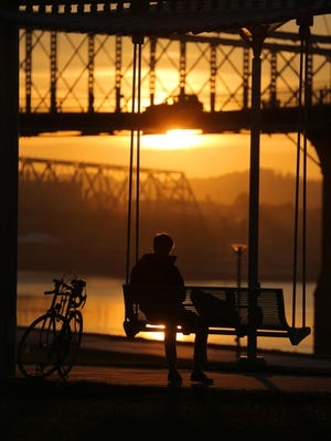 A visitor watchs the sunrise from Smale Riverfront Park.