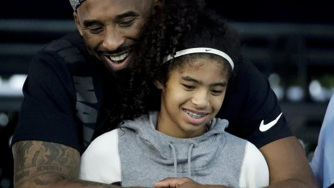 FILE - In this July 26, 2018 file photo former Los Angeles Laker Kobe Bryant and his daughter Gianna watch during the U.S. national championships swimming meet in Irvine, Calif. Bryant, the 18-time NBA All-Star who won five championships and became one of the greatest basketball players of his generation during a 20-year career with the Los Angeles Lakers, died in a helicopter crash Sunday, Jan. 26, 2020. Gianna also died in the crash. She was 13.