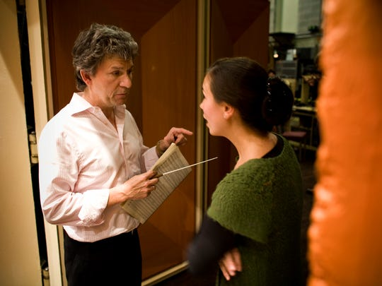 Former music director Andreas Delfs returns to the Milwaukee Symphony Dec. 1-3 to conduct four holiday concerts. In this 2009 photos, Delfs talks with trombonist Megumi Kanda during a rehearsal.