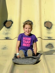 Laney Triplett, 8, of Yerington,is all smiles as she takes a ride down the Super Slide.