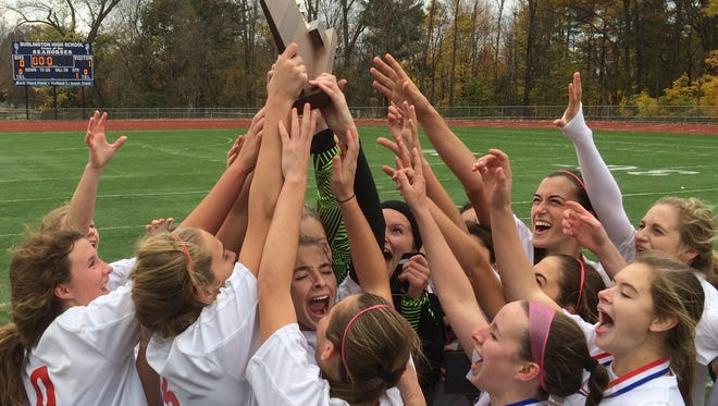 The Champlain Valley girls soccer team lifts the Division I state championship trophy Saturday after a 1-0 victory against Burlington. It's the Redhawks fourth championship in as many years.