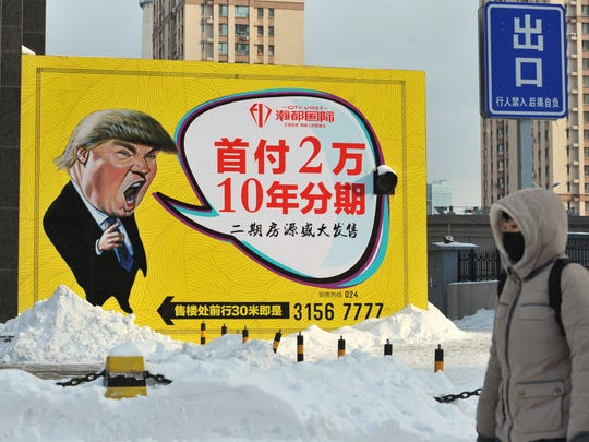 A pedestrian walks past a real estate advertisement