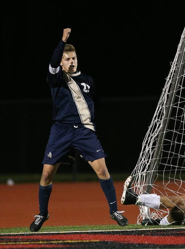 Pittsford Sutherland's John Mozrall celebrates his late goal as Honeoye Falls Lima's Luis Playa slides into the goal.  Sutherland beat HFL 2-0 to win the Class A2 championship.