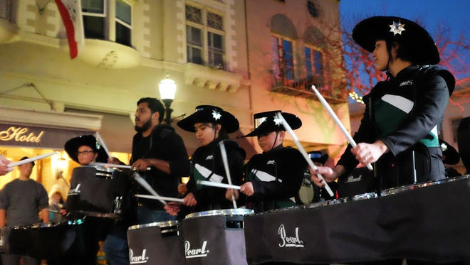 Turning the corner onto Alvarado St., the ACAN/AUSD All-Star Drumline from east Salinas leads off the First Night Monterey Twilight Procession. Guiding the group are instructor Rich Andrade, second from left, and Yvette Ayala, in uniform at right.