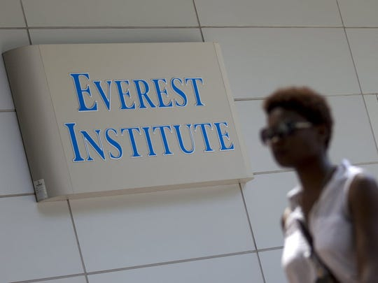 A woman walks past an Everest Institute sign in an