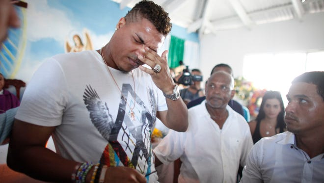 Cincinnati Reds pitcher Alfredo Simon grieves during the funeral of St. Louis Cardinals outfielder Oscar Taveras in Sosua, Dominican Republic, on Oct. 28, 2014.