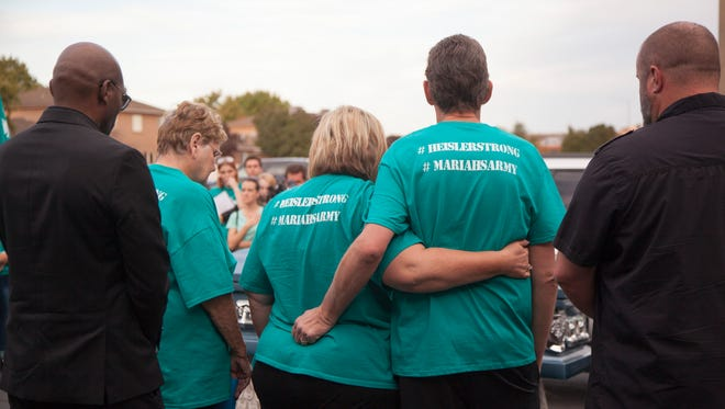 Family and friends gather to honor David Heisler as his body is transported to the funeral home Friday, Oct. 14, 2016.