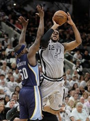 San Antonio Spurs forward LaMarcus Aldridge (12) shoots over Memphis Grizzlies forward Zach Randolph (50) during the second half in Game 1 of a first-round NBA basketball playoff series, Saturday, April 15, 2017, in San Antonio.