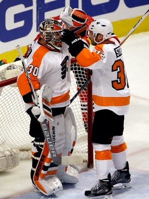 Flyers goalie Michal Neuvirth, left, celebrates with Mark Streit after they defeated the Chicago Blackhawks on Wednesday.