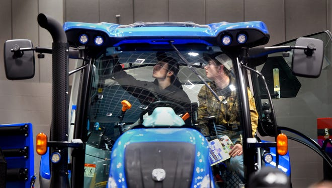Ryan Chock and Jacob Barton check out the features of a new tractor Tuesday, Feb. 28, during the Central Minnesota Farm Show held at the River's Edge Convention Center in St. Cloud.