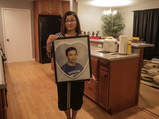 Ester Kiim holds a portrait of her late husband, Stephen Kim, who was shot and killed last April in Des Moines. With help from life insurance and generous donations from the Des Moines community, Kim and her sons were able to buy a home in Clive.