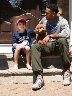 "Brendan O'Callaghan, one of the victims of the Paramus bus crash, came home from the hospital on Tuesday May 29, 2018.  O'Callaghan sits on the front steps to his home with his dog ""Chewey"" and Romeo Okwara, one of the Giants."