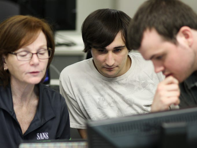 Lincroft, NJ - From left, Mandy Galante, Christian Nicholson, and Mike Calfin at a session of the Cyber Aces program at Brookdale Community College. The program teaches students how to detect cyber attacks on U.S. institutiuons and infrastructures.