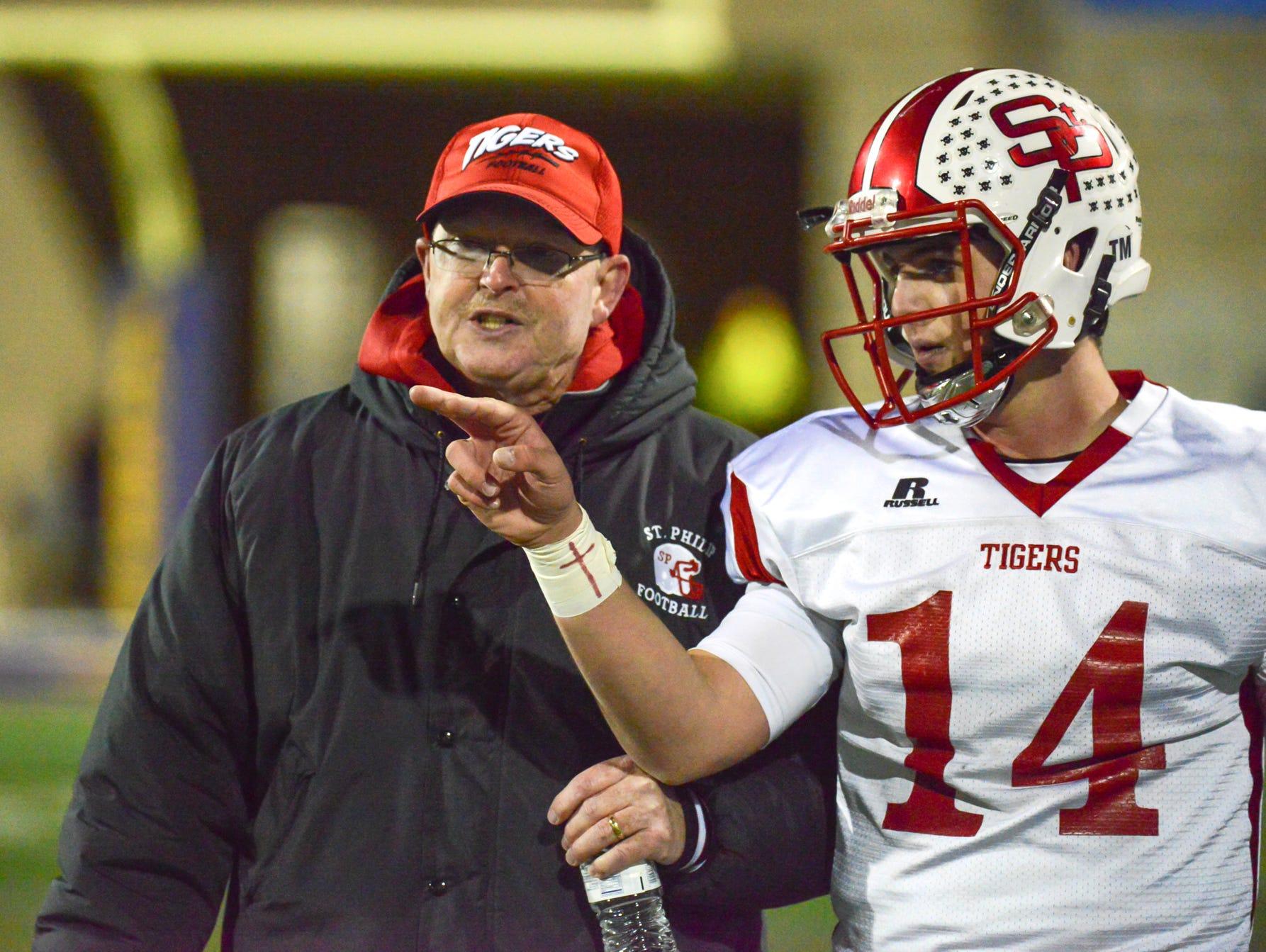 St. Philip quarterback Brendan Gausselin talks with head coach David Downey during a break in action Friday night.