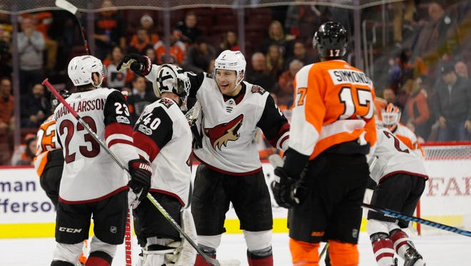 Arizona Coyotes' Luke Schenn, center right, celebrates the win with Scott Wedgewood, center left, and Oliver Ekman-Larsson, of Sweden, left, as Philadelphia Flyers' Wayne Simmonds, right, looks on following the overtime period of an NHL hockey game, Monday, Oct. 30, 2017, in Philadelphia.