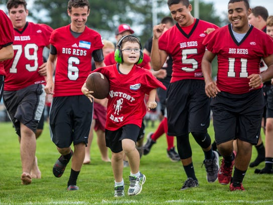 James Ursitti, 8, smiles as he sprints down field to