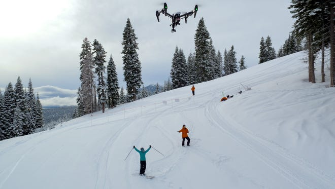 A Cape Productions drone flies over skiers while recording their runs down the slopes.