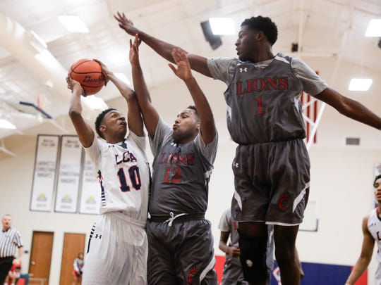 Lafayette Christian's Pierre Dupre shoots against Covenant Christian's Justin Jackson and Devante Johnson in first half action of the Quarterfinals game in Lafayette Thursday, March 2, 2017.