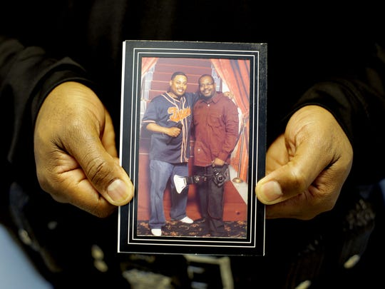 Mark D. Wallace, a Detroit police officer, holds a photo of  him, left,  and his former police partner, Sidney Taylor, who died last year Dec. 31, 2014 at the age of 49.