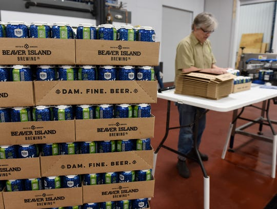 Brewmaster Chris Laumb stacks cases of freshly canned
