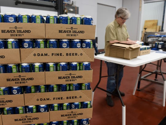 Brewmaster Chris Laumb stacks cases of freshly canned Ripple beer off the line Wednesday, May 24 on the first day of production at the new Beaver Island Brewing Co. facility in St. Cloud.