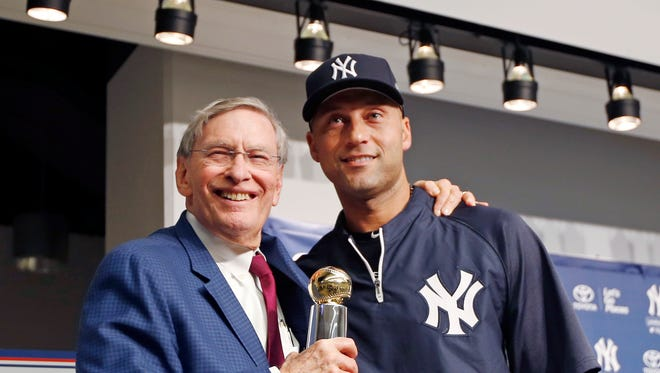 Major League Baseball Commissioner Bud Selig, left, poses for a picture with Yankees shortstop Derek Jeter after presenting Jeter with the Commissioner's Historic Achievement Award before a baseball game between the Yankees and the Baltimore Orioles at Yankee Stadium in New York, Tuesday, Sept. 23, 2014.  (AP Photo/Kathy Willens)