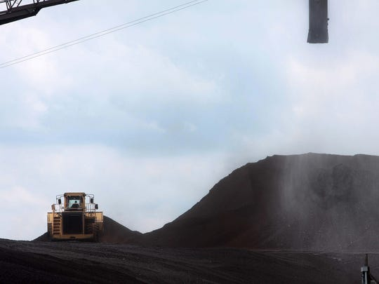 A large piece of equipment moves coal from a larger