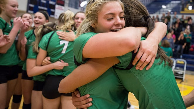 Bella Rosenthall gets a hug from her fellow teammate Saturday after a narrow win during sectional finals. Yorktown won won the fifth set 19-17 and defeated Delta 3-2.