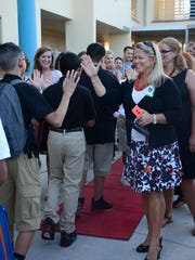 Manatee Middle School Principal Pamela Vickaryous, right, leads the faculty in greeting students with a red carpet and high-fives on the first day back to school in Collier County in this 2015 file photo.