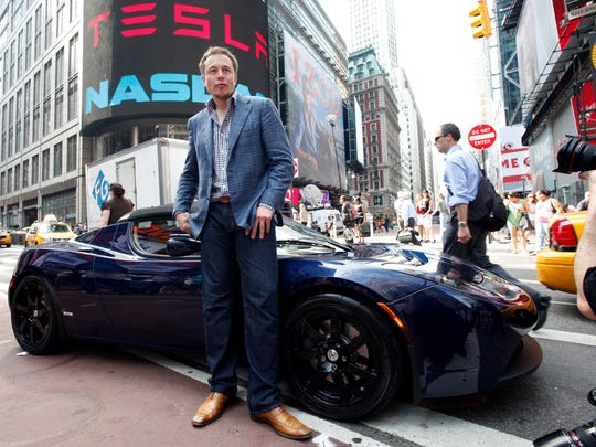 "Elon Musk, CEO of Tesla Motors, poses with a Tesla car in front of Nasdaq following the electric automakerís initial public offering on June, 29, 2010, in New York. The company plans to trade on the Nasdaq stock exchange under the ticker ""TSLA."""